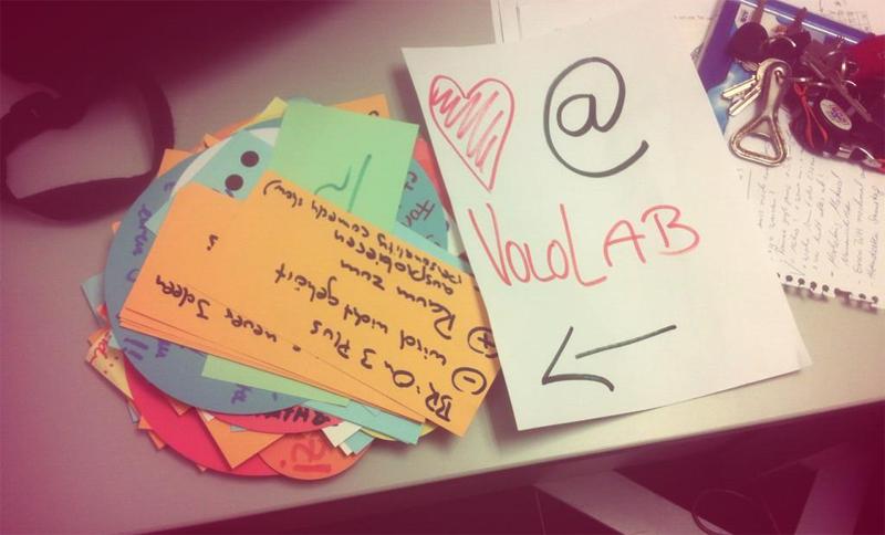 """Ein Zettel mit der Aufschrift """" Herz @ Vololab"""" auf einem Tisch"""