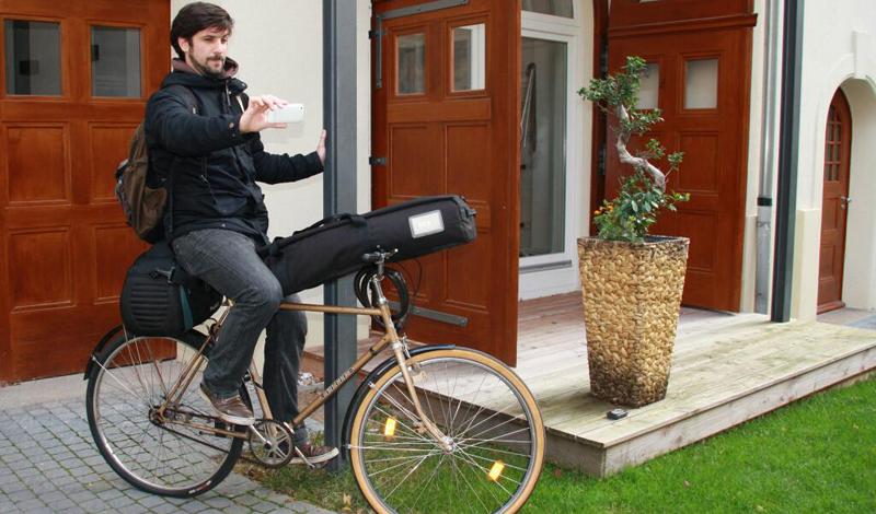 Mann auf einem Fahrrad mit VJ-Kamera, Rucksack, Stativ und Smartphone in der Hand
