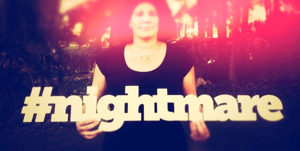 Eine Frau hält das Wort #nightmare in den Händen